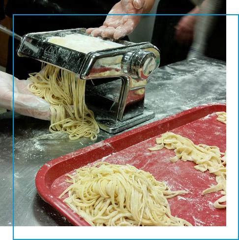 Two hands machine cutting fresh egg pasta