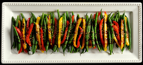 Green beans and peppers seasoned on a rectangle white dish