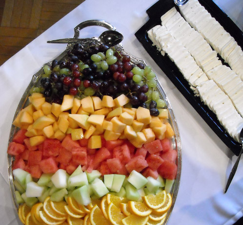 Assortment of fresh fruit in a large silver bowl with a plate of slided Feta cheese