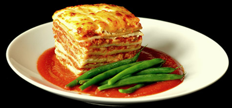 Lasagna and green beans on a white plate