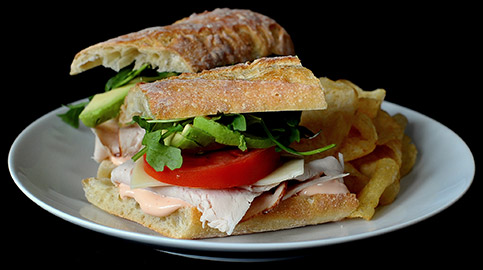 Turkey sandwhich with lettuce and tomato on a white plate with potato chips